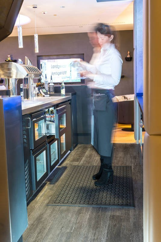 Bar server behind a bar standing on a single piece of Morland Service Anti bacterial rubber industrial doormat