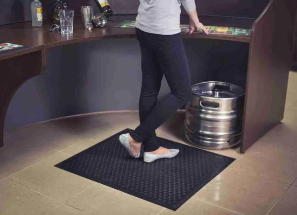 Woman behind a bar standing on a Morland Comfort Active Industrial Rubber Door Mat