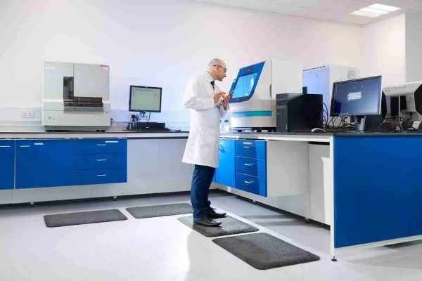 Man in a lab coat standing on a Morland Comfort Soft Top anti-fatigue mat
