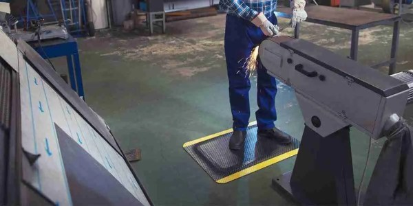 A worker standing at an industrial workstation on Morland Comfort Safety Anti fatigue mat