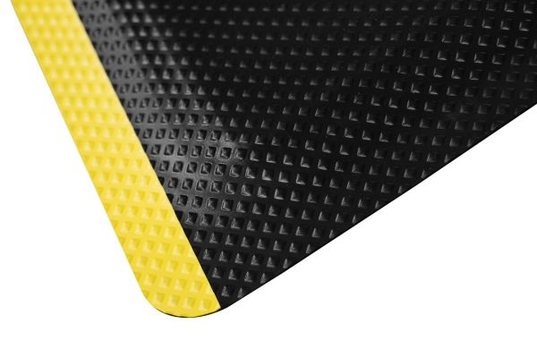 A close up of the corner of a Morland Comfort safety anti-fatigue mat showing yellow stripe and cushioned centre
