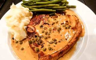 pork chop with mustard sauce on white plate