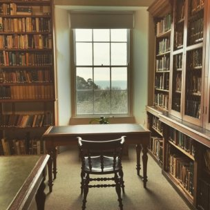 A reading room in The Morrab Library, with a view out of the window across the Morrab Gardens to Mount's Bay