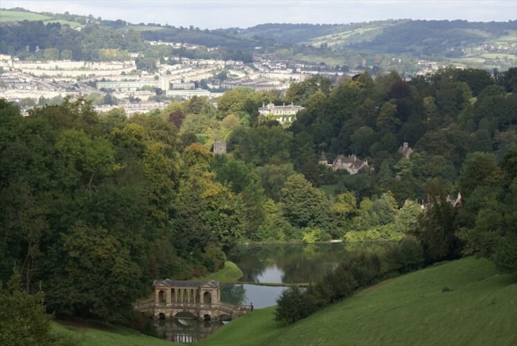 A view of the steep-sloped Prior Park, with the Palladian bridge and lake, and the house beyond.
