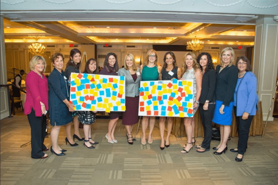 Twelve business women holding two signs at an event