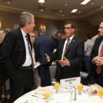 four business men talking at a networking event