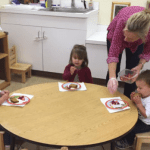three children eating a health snack at school