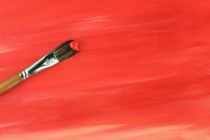 Paintbrush against a red abstract painting.