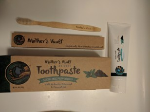 tube of toothpaste and box, bamboo toothbrush and box