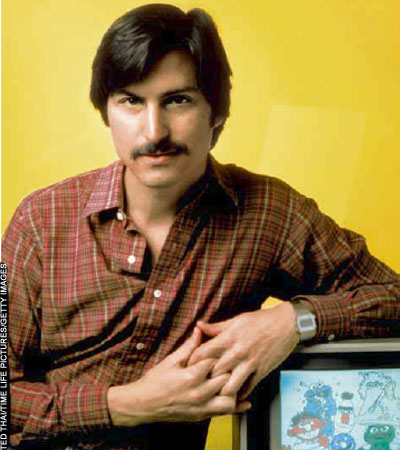 Steve Jobs with a mustache, leaning on a monitor showing Sesame Street Muppets