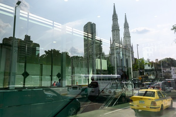 Passengers walking into the Panama City Metro subway at the Iglesia del Carmen station, with the namesake church reflected in the glass.