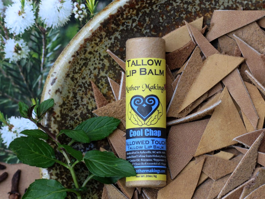 Yellow and glacier blue labeled tallow lip balm in a dish of cut tan leather with a sprig od peppermint and a photo of an Australian Melaleuca flower and cloves.