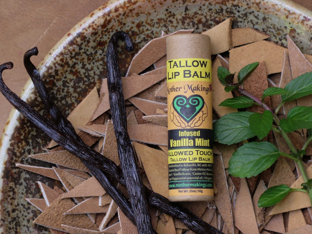 Infused vanilla Mint tallow lip balm in a paper tube laying in a dish of cut tan leather with 3 black vanilla beans and a deep green peppermint sprig