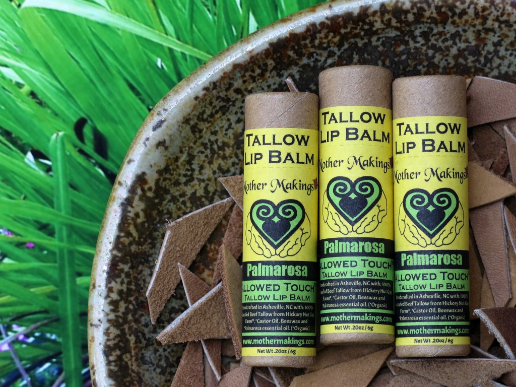 3 yellow and green Palmarosa tallow lip balm in biodegradable paper tubes in a dish of cut tan leather with spring green palmarosa grass in the background.