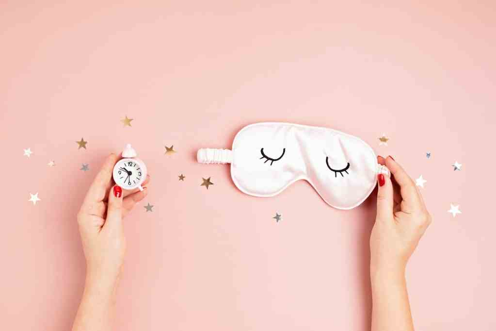 Sleeping mask and classic alarm clock on pink pastel background. Minimal concept of rest, quality of