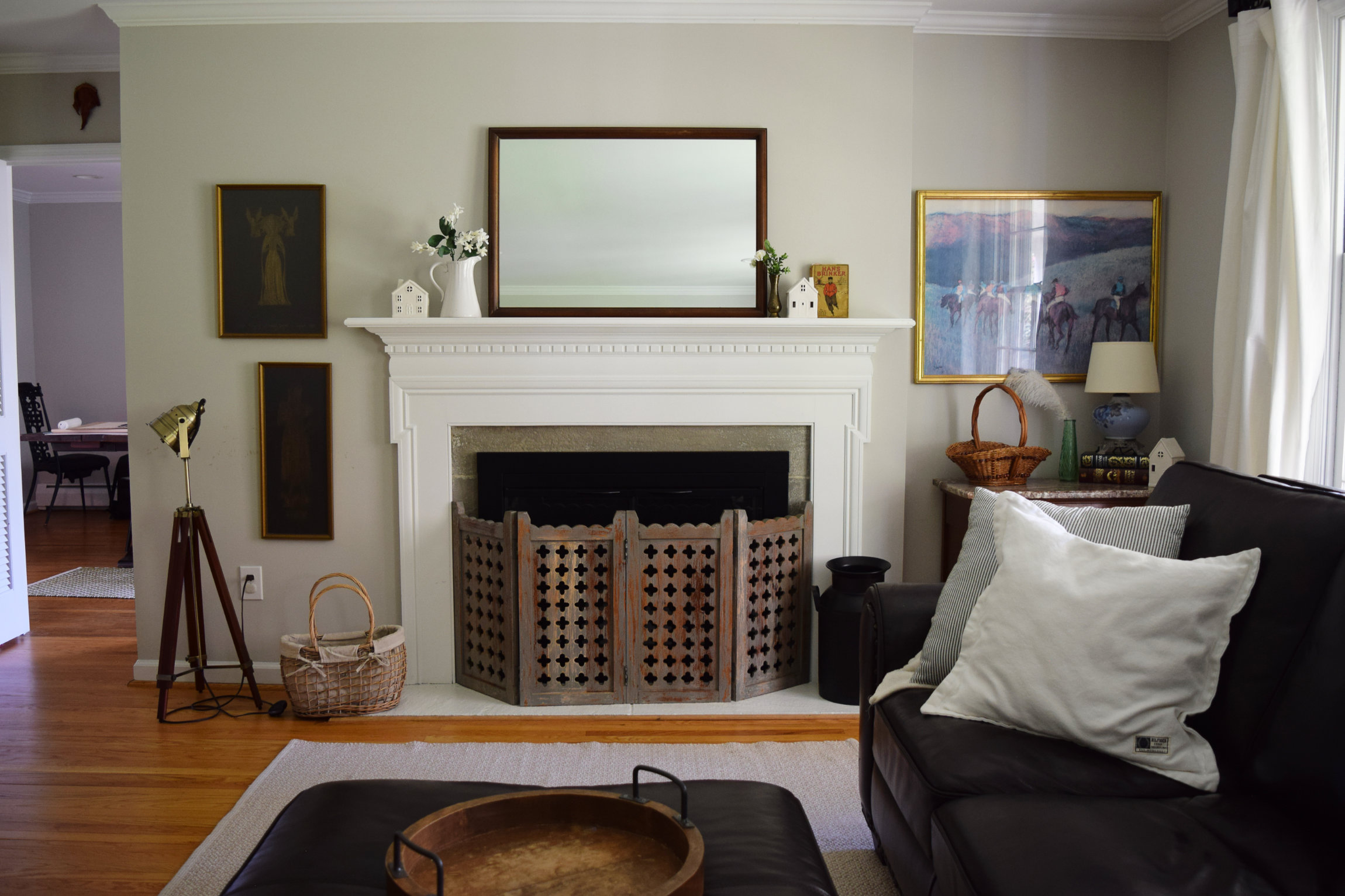 gray living room with mirror on mantel and dark leather sectional
