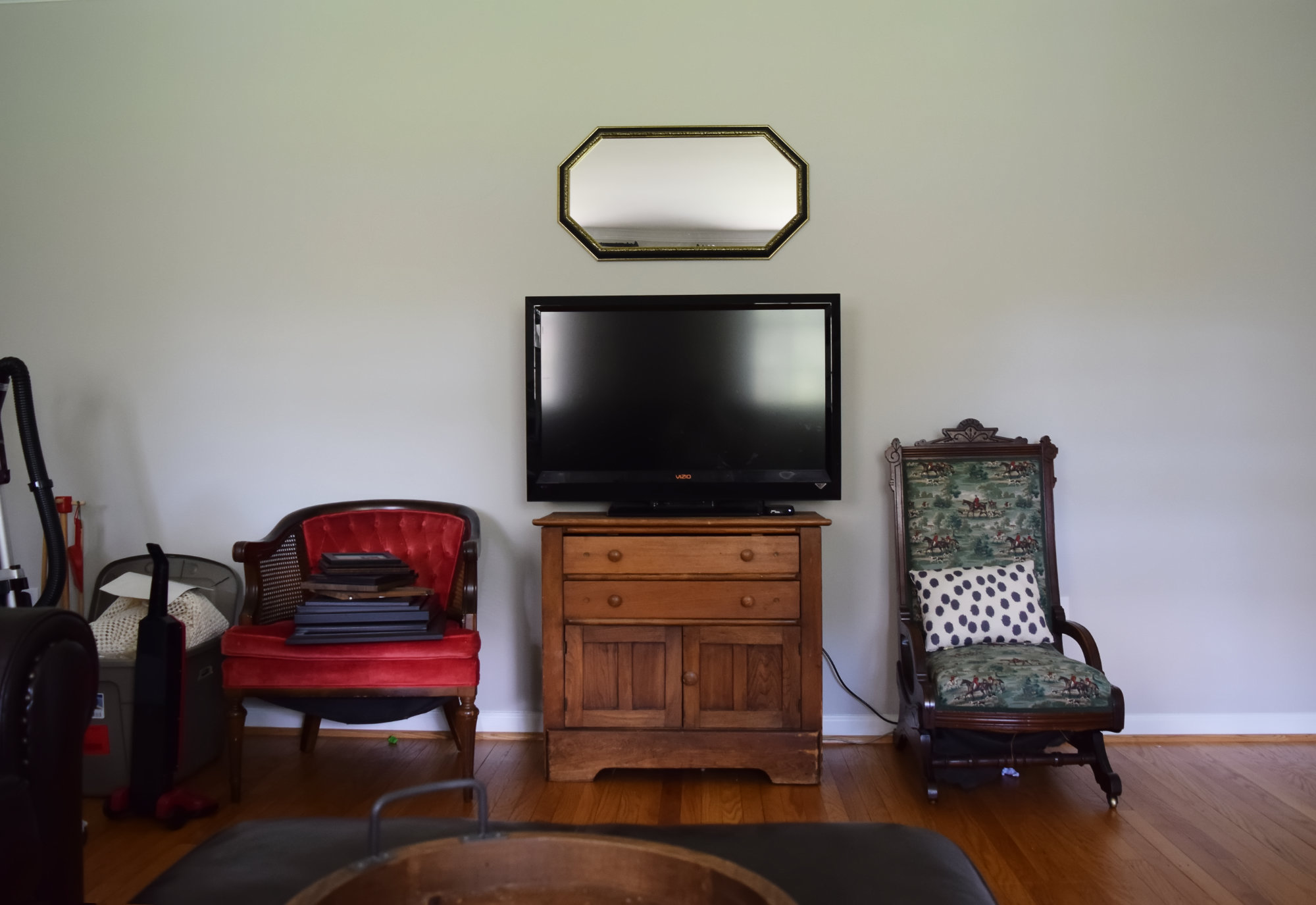 tv on old cabinet between red tufted cane chair and equestrian toile chair with polka dot pillow