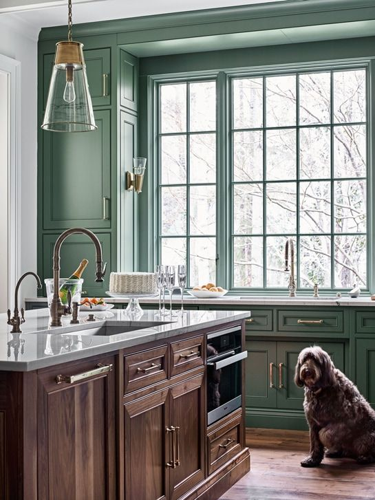 green bank of kitchen cabinets and window grilles with dark wood and brass