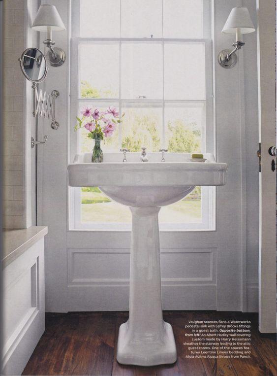 pedestal sink in window with accordion makeup mirror