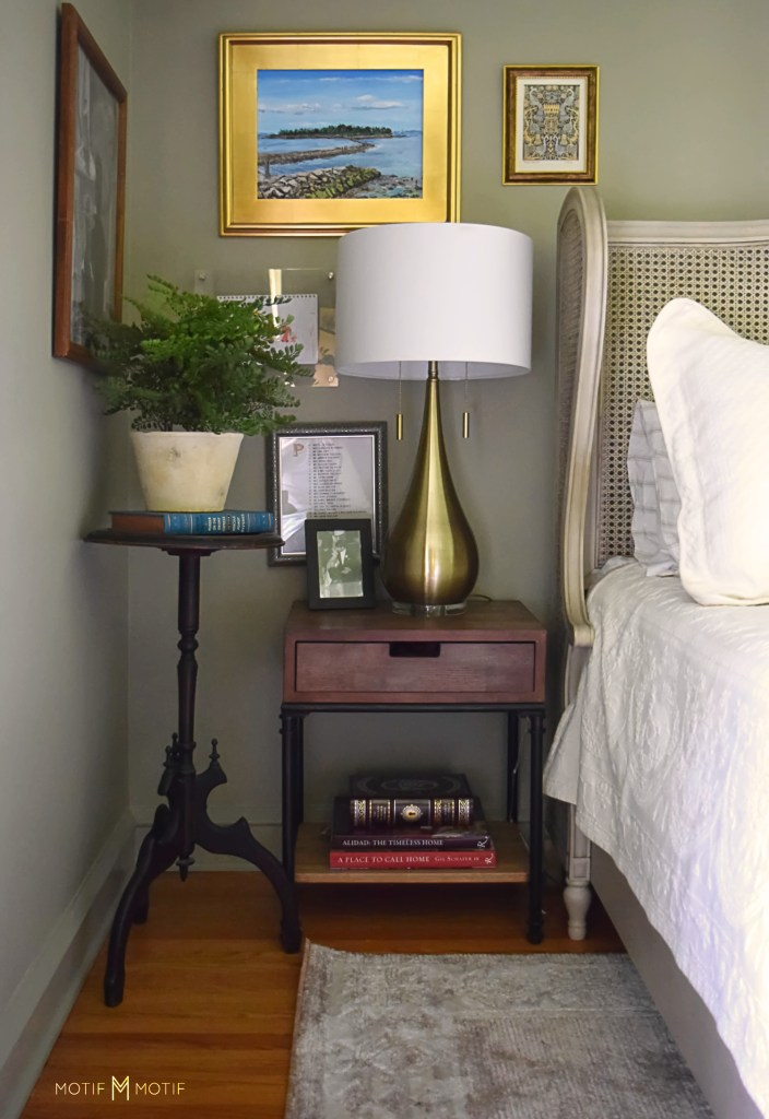 gold lamp on bedside table with potted plant on stand and books