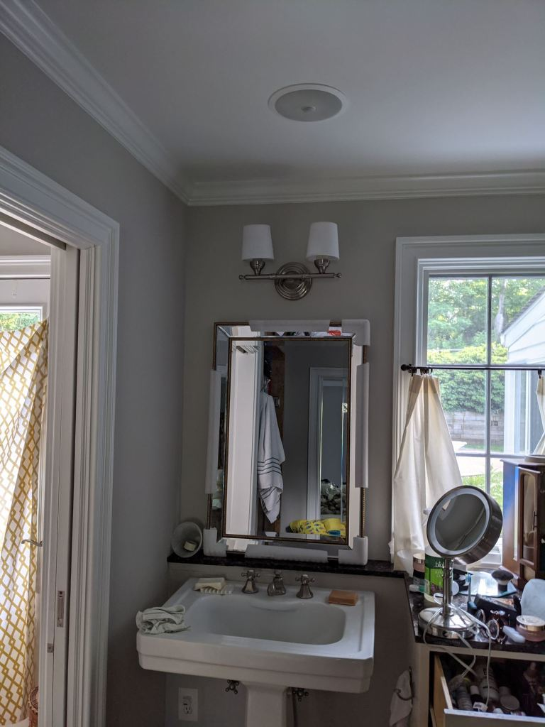rotated vanity sconce with linen shades uplight