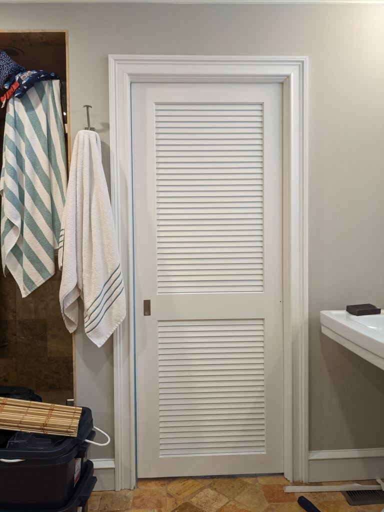 louvered door leading to water closet before