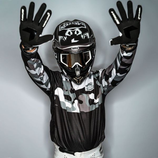 Model wearing white camo motocross jersey, gloves and helmet with hands in the air