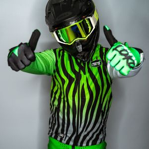 Front view of model wearing green bodywarmer, gloves and helmet with both thumbs up