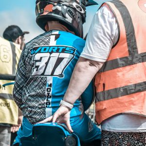 photograph of the back of a boy sitting on a motocross bike showing jersey customisation