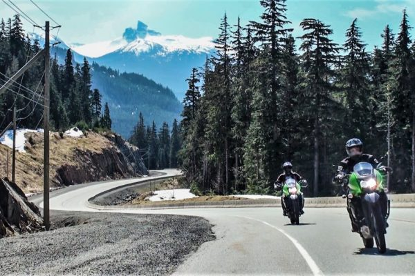 Riding a motorcycle with Black Tusk mountain in the backgrounf