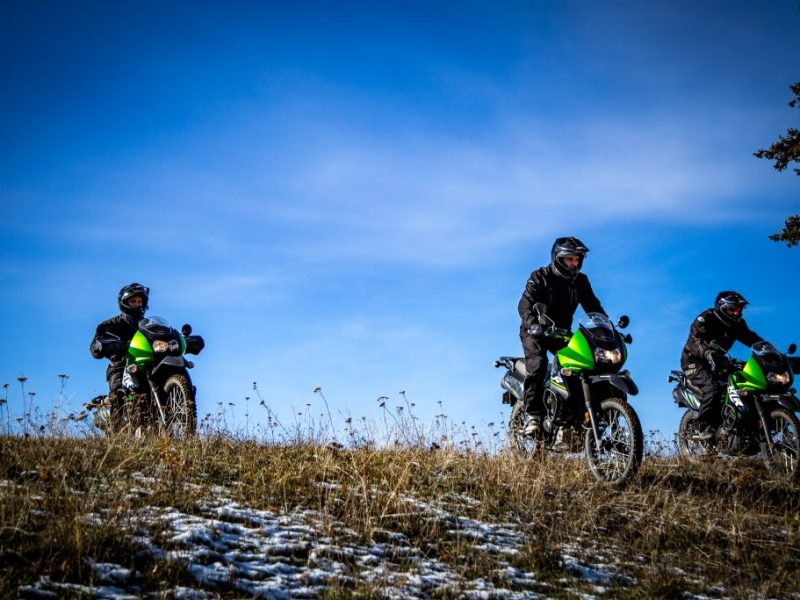 3 KLR MOTORCYCLES COMING OVER A SLIGHTLY SNOWY HILL DURING A CUSTOM TOUR