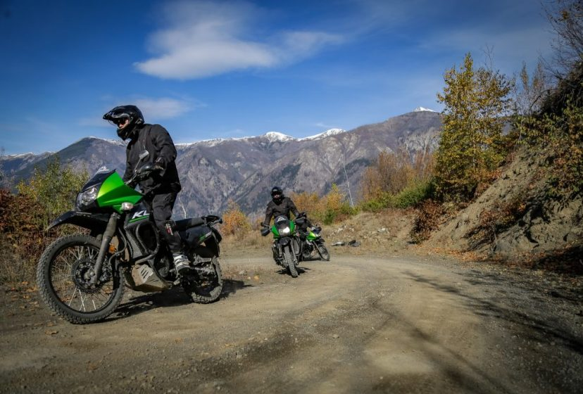 Motorcycle riding up a dirt road into the sky with mountain shadows and bright blue sky in the background