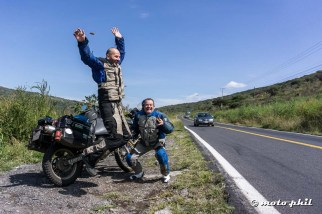 moto.phil and Charly jumping in front of their motorcycles beside the road