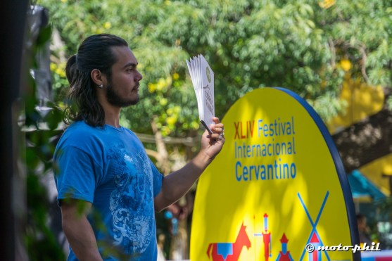 Man holding up menues in front of Festival Cervantino sign