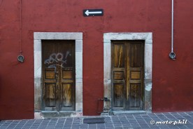 Two old wooden doors on red wall with an arrow sign above