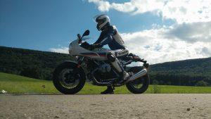 BMW R nineT Racer in weiß-blau-rot und Biker in Lederkombi blau-weiß