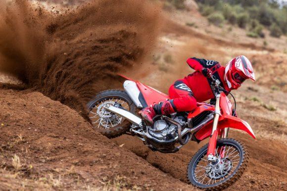 A red-clad rider pushes a red 2022 Honda CRF250R dirt bike through the dirt