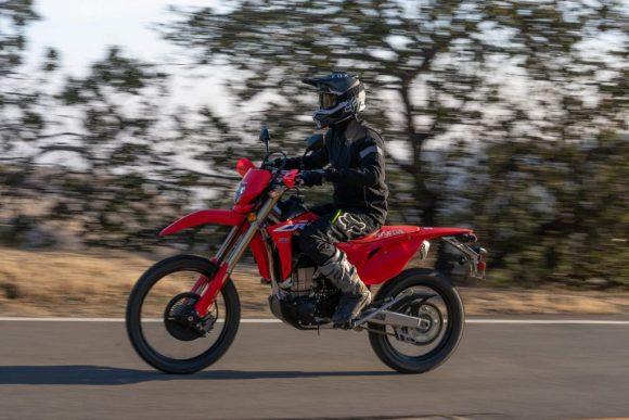 A black-clad rider rides a red 2022 Honda CRF450L dirt bike down a paved road