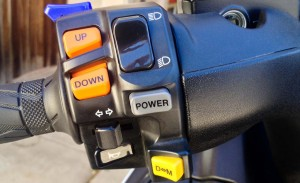 """The Burgman's many options are (from top to bottom): mirror fold switch (blue), thumb shifting (orange), power mode switch (gray), and drive/manual """"shift"""" mode (yellow)."""
