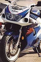Four-piston calipers and a conventional fork are fitted. The GSX-R750 uses upside-down forks and six-piston brakes, costing about $1300 more.