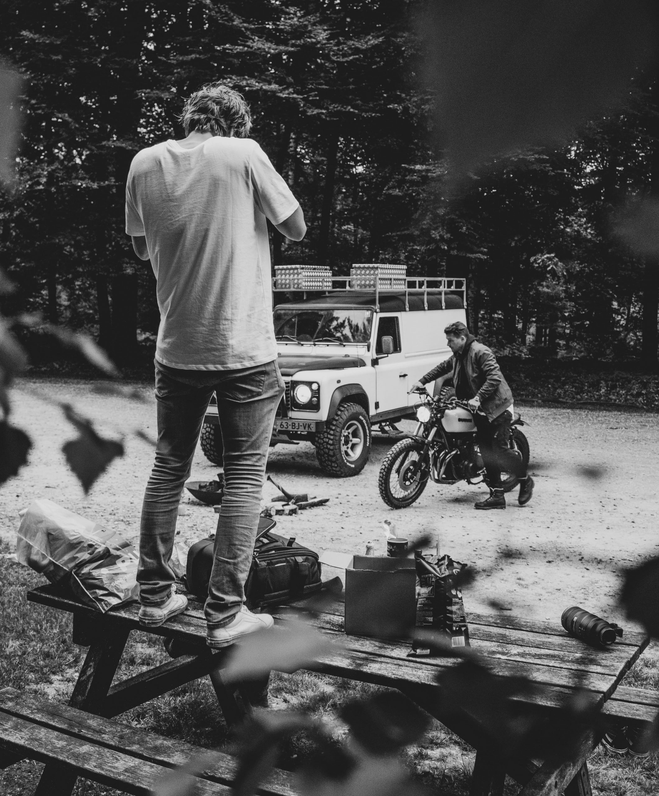 Photographer taking image of biker stood on a bench documenting motorcycle trip