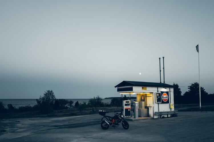 motorcycle at fuel stop - motorcycle touring on a budget