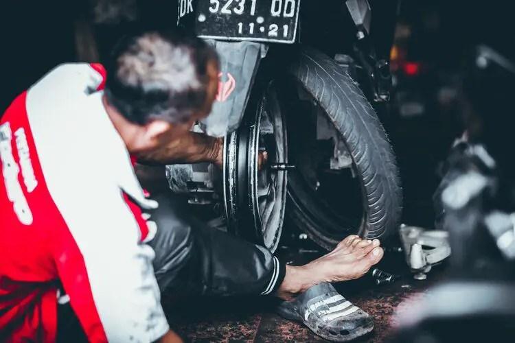 Malaysian mechanic changing motorcycle tyre
