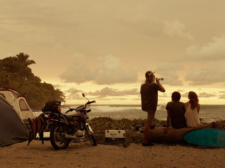 group of friends, motorcycle and tent at sunset