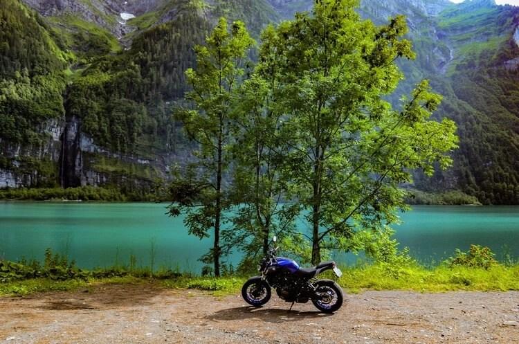 motorcycle next to turquoise lake