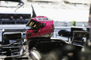 Jenson Button's helmet waits on the top of his car in the garage.