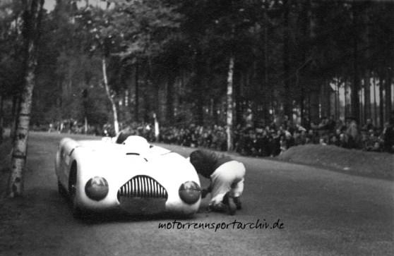 Theo Helfrich hat den Wagen auf der Rennstrecke angehalten und macht sich an die nicht ungefährliche Behebung des Reifenschadens. Der Erdwall rechts dient übrigens der Streckensicherung.
