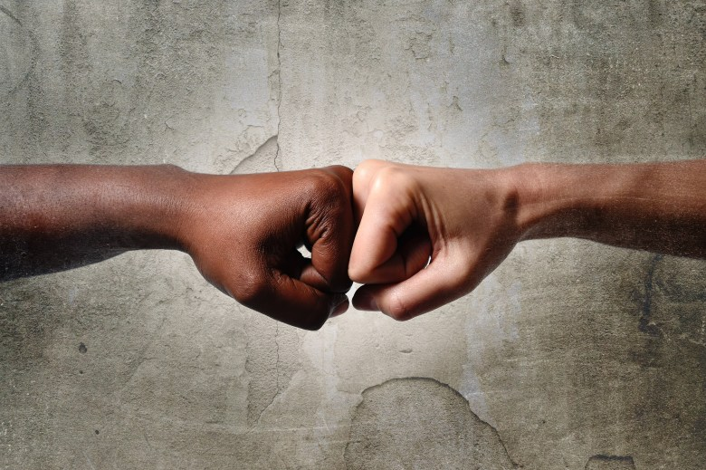 black African American race female hand touching knuckles with white Caucasian woman in agreement partnership and cooperation multiracial diversity immigration concept