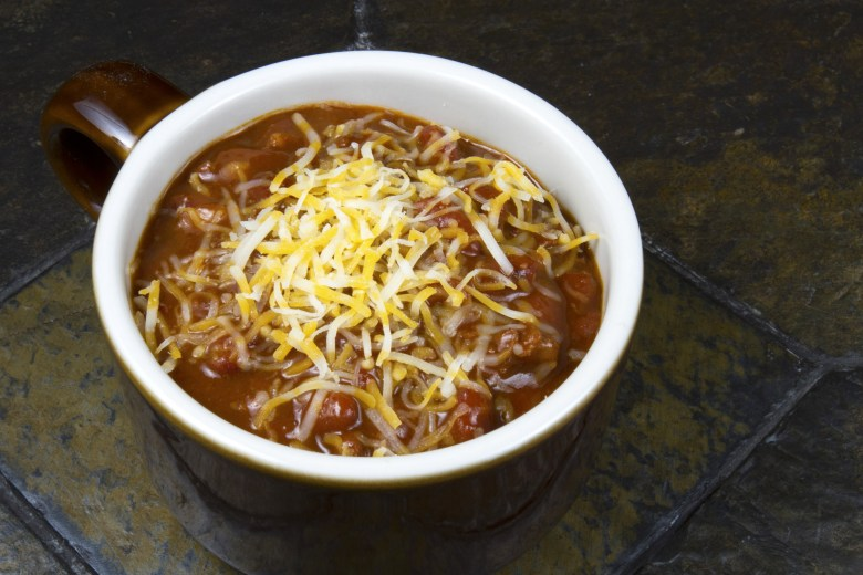 Chili con carne covered in melted cheese in rustic crockery