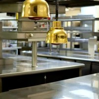 Empty restaurant kitchen with staineless steel tables and copper lighting